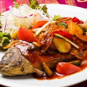 名古屋駅(名駅)にある本格タイ料理店「マイペンライ」で夜ご飯におすすめ。丸ごと揚げたティラピアに色とりどりの野菜とパイナップル&トマトソースで仕上げた甘酢あんかけをかけて提供する「ティラピアの姿揚げタイ式甘酢ソースがけ」の画像