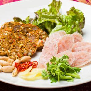 名古屋駅(名駅)で夜ご飯なら本格タイ料理店「マイペンライ」。当店おすすめ。米、塩などを発酵させた程よい酸味のネームソーセージとハーブが効いたスパイシーなチェンマイソーセージの盛合せの画像