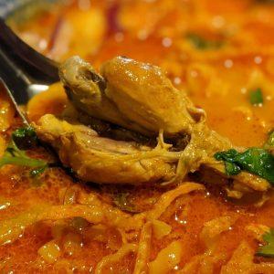名古屋駅(名駅)でランチなら本格タイ料理店「マイペンライ」。平打ちの中華麺を使った親しみやすいカレースープに柔らかく煮込んだチキン、パリパリの揚げ麺、からし菜ピクルなどトッピングして仕上げたおすすめご飯「カオソーイ・チキン」の画像